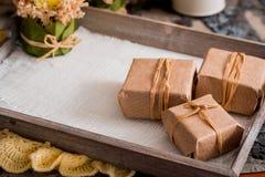 Trois boîte-cadeau dans un emballage de papier d'emballage sur un fond concret gris sur une table en bois endroit pour votre insc photo stock