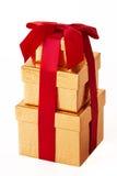 Trois boîte-cadeau enveloppés par or Images stock
