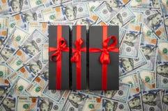 Trois boîte-cadeau noirs avec l'arc sur le fond des dollars photographie stock libre de droits