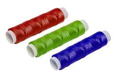 Trois bobines de coton de RVB d'isolement sur le fond blanc Photographie stock libre de droits