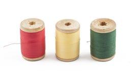 Trois bobines multicolores en bois d'amorçage sur le blanc Image stock