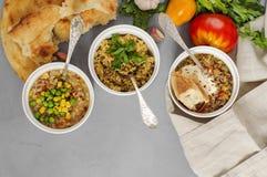 Trois bols de haricot, de soupe à quinoa et de bulgur de champignon sur un b gris Images stock