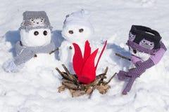Trois bonhommes de neige mignons autour d'un feu de camp Photographie stock