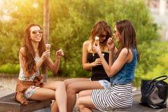 Trois bonnes amies mangent la crème glacée sur un banc dans la ville Photo stock