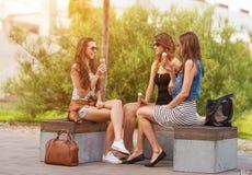 Trois bonnes amies mangent la crème glacée sur un banc dans la ville Images stock