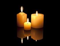 Trois bougies brûlantes avec la réflexion Image stock