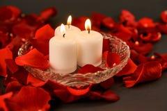 trois bougies brûlantes se tiennent dans des pétales de rose rouges images libres de droits