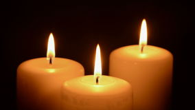 Trois bougies brûlant sur un fond noir banque de vidéos