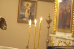 Trois bougies dans l'église orthodoxe Le rite traditionnel du baptême photo stock