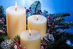 Trois bougies dans un agencement de fleur d'arrivée Image stock