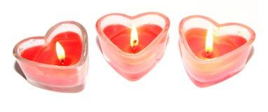 Trois bougies en forme de coeur rouges Images stock