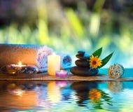 Trois bougies et serviettes noircissent les pierres et la marguerite orange sur l'eau Image stock