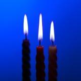 Trois bougies sur le bleu Image stock