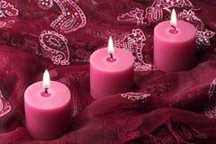 Trois bougies sur le tissu pourpré Image stock