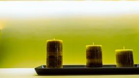 Trois bougies vertes sur le plateau en plastique noir ont mis dessus la table blanche Images libres de droits