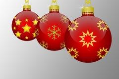 Trois boules accrochantes rouges d'arbre de Noël avec les flocons de neige et les ornements d'or d'étoiles sur un fond gris Photos libres de droits