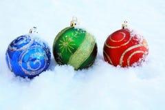 Trois boules colorées de Noël dans la neige Photos stock