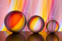 Trois boules de cristal en verre dans une rangée avec un arc-en-ciel de la peinture légère colorée derrière eux photographie stock