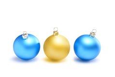Trois boules deux de Noël bleues et un jaune Images libres de droits