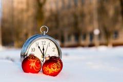 Trois boules et horloges rouges de Noël sur une neige Photographie stock