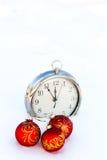 Trois boules et horloges rouges de Noël sur une neige Photographie stock libre de droits