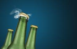Trois bouteilles à bière vertes sur le fond bleu Photographie stock