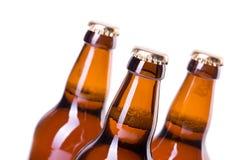 Trois bouteilles de bière glacée d'isolement sur le blanc Photographie stock libre de droits