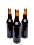 Trois bouteilles de bière sur le fond blanc. Photo stock