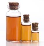 Trois bouteilles de liquide brun Photos stock