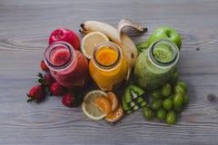Trois bouteilles de smoothies de fruit frais toned Images stock