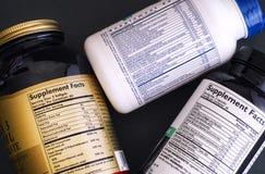 Trois bouteilles de supplément diététique avec des labels de faits de supplément Image stock