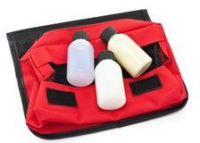 Trois bouteilles de taille de course sur un sac d'articles de toilette Images libres de droits