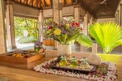 Trois bouteilles en verre avec le pétrole et les fleurs aromatiques sur la table en bois à la STATION THERMALE Images libres de droits