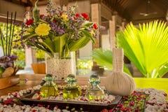 Trois bouteilles en verre avec le pétrole et les fleurs aromatiques sur la table en bois Images stock