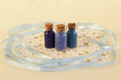 Trois bouteilles en verre minuscules avec du liège bouchent, rempli de couleurs bleues des perles, de la serviette et du ruban bl photographie stock
