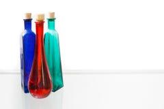 Trois bouteilles vides colorées sur le fond blanc Photos libres de droits