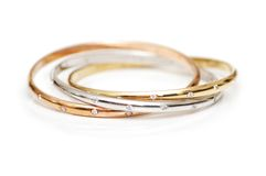 Trois bracelets d'or d'isolement Photographie stock