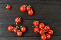 Trois branches des tomates-cerises rouges d'isolement sur le fond en bois noir Images libres de droits