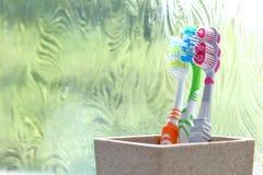 Trois brosses à dents dans un culbuteur d'argile à la lumière d'une fenêtre obscurcie Photos stock