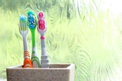 Trois brosses à dents dans un culbuteur d'argile dans la lumière de matin d'une fenêtre obscurcie Photo libre de droits