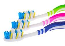 Trois brosses à dents neuves Photos stock