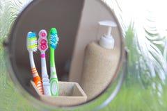 Trois brosses à dents reflétées dans un miroir Photographie stock libre de droits