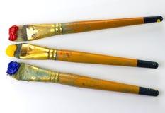 Trois brosses avec la peinture rouge, jaune et bleue sur le fond blanc Endroit pour le texte, pour la bannière, pour le site Photographie stock