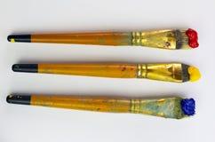 Trois brosses avec la peinture rouge, jaune et bleue sur le fond blanc Endroit pour le texte, pour la bannière, pour le site Image libre de droits