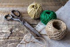 Trois bruns et boule verte de fil avec des ciseaux antiques de vintage sur de vieux conseils en bois texturisés Rustique, couture Image libre de droits