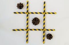 Trois cônes de sapin bruns se situent dans une rangée dans un jeu de tic-TAC-orteil, dans une grille sur un fond blanc La grille  photographie stock libre de droits