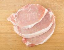 Trois côtelettes de porc crues Photographie stock libre de droits