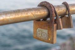 Trois cadenas rouillés d'amour au-dessus de la mer Photographie stock