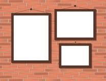 Trois cadres bruns vides sur le mur de briques rouge illustration stock