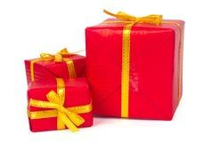 Trois cadres de cadeau rouges avec des proues et des bandes de jaune Photographie stock